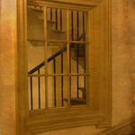 a photograph of a view through a window to a staircase with a balustrade