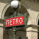 A photograph of a red, Art Deco Metro sign surmounted by a globe-shaped lamp 