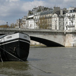 A photograph of a barge on the river Seine in Paris with fine stone houses and bridge