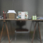 photo of a work table with papers and pencils stacked on it viewed through frosted glass