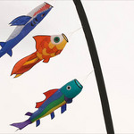 photo of three paper kites in the shape of fish - attached to a pole and blowing in the wind