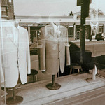 photo of a window looking in with suits and shirts on display