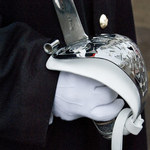 photo of a soldier in a black coat with white gloves holding a sabre upright at attention