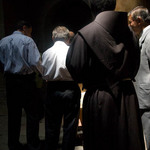 photo of priest in brown habit standing with other men observing silence in the Church of the Holy Sepulchre in Jerusalem