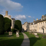 a photograph of a churchyard with yew trees, with stone cottages in the street beyond in  the Cotswolds, England