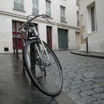a photograph of a bicycle lying against a bollard in a street in Paris