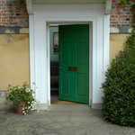 A photograph of a green door and open doorway and view into the hall of a Regency building in Lincoln, England