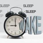 alarm clock with text reading: 'Sleep, sleep, sleep, WAKE UP!'