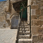 photo of the roof of the Church of the Holy Sepulchre in Jerusalem showing a small battered staircase and a cross