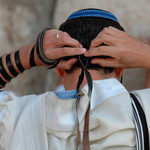 photo of a man tying head tefillin, phylacteries while praying at the Western Wall in Jerusalem