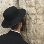 photo of a man in a black suit with payot (side curls) praying against the Western Wall in Jerusalem