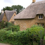 a photograph of a thatched cottage in the village of Great Tew, Oxfordshire, England